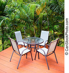 Table and chairs on the veranda in a tropical garden