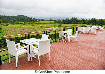 Table and chairs outdoor restaurant / Set of white dining table on terrace and view nature and mountains countryside