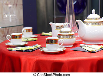 Table appointments on red tablecloth. Accent focus on front.