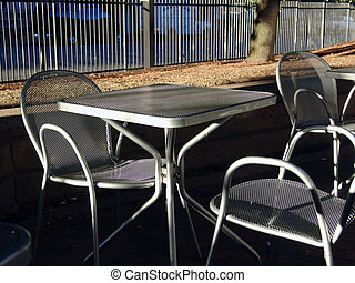 Table at outdoor cafe - sunlit empty table at out door cafe...