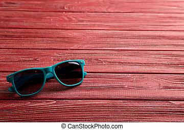 table bois, lunettes soleil, rouges