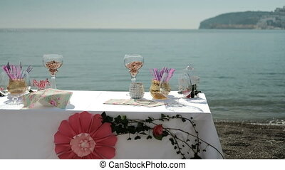 table by sea with sweet things snacks, drinks for banquet on fresh air