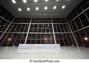 Table covered with white tablecloth in large, spacious, empty lobby