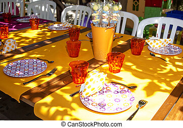Table decorated with colorful tablecloths and crockery