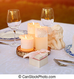 Table decorated with candles and angels for wedding or romantic dinner. Gift box with wedding rings, proposal or marriage concept