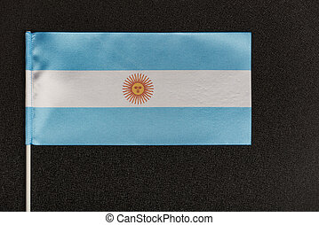 Table flag of Argentina on black background. Blue-white flag with sun