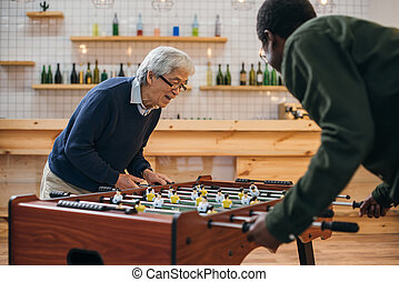 table football - happy senior friends playing table football...