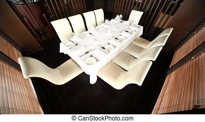 Table for ten persons stands in separate room separated by...