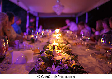 table for wedding reception with candles on nature in evening