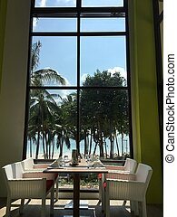 Table in front of a window with beach view