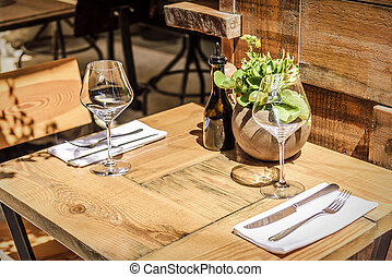 Table in the restaurant in the open air with glasses of...