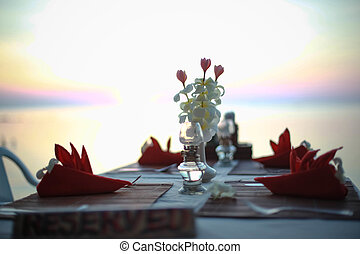 Table in the restaurant on the sea background decorated of flowers. Table is ready for Dinner at the Beach