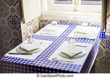 Table in traditional Portuguese restaurant ready for four people