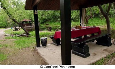 Table is set in summerhouses ashore of small pond at among trees at summer