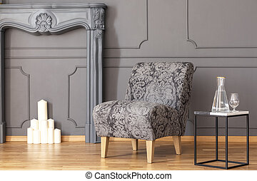 Table next to grey armchair in elegant living room interior...
