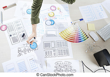 Wireframes of future project, paper samples of icons and color palette on table of UI designer
