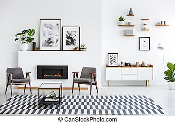 Table on patterned carpet in white living room interior with grey armchairs and posters. Real photo