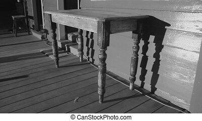 Table outside the house in black and white - A medium shot...