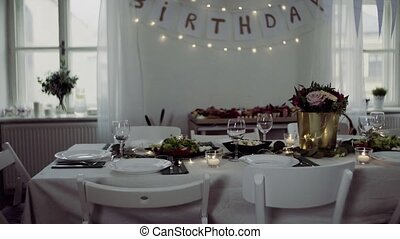 Table set for a meal indoors in a room on a birthday party,...