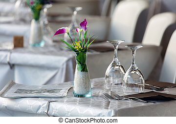 Table set with flowers, glasses, napkins and forks