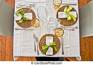 table set with plates and cutlery and glasses and a beautiful green bow