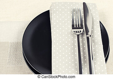 Table setting: black plate, fork and knife with napkins on...