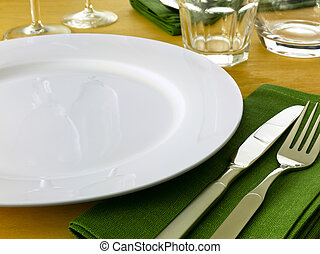 Table setting complete with plate knive and fork glasses and napkins on a light wooden table.