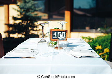 Table setting in a restaurant on the summer terrace. Tablet on the table one hundred