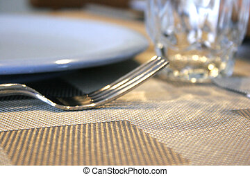 Soft Focus of a table setting fork knife and glass
