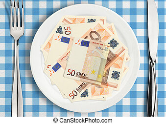 Table setting with money on plate, finance concept