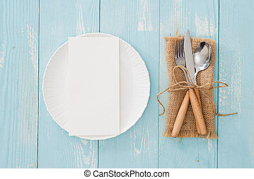 Table setting with plate, fork and knife on wooden background