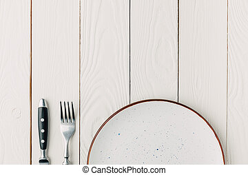 Table setting with plate on white wooden background
