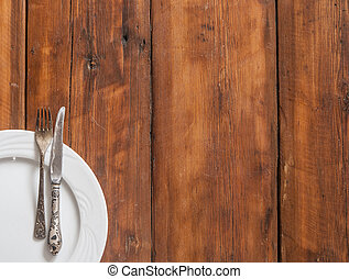 Table setting with vintage silverware or cutlery and empty plate on rustic wood. Top view with copy space for text