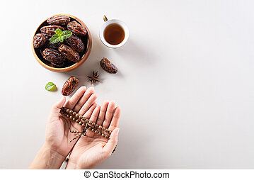 Table top view image of decoration Ramadan Kareem background,  dates fruit, coffee and hand with rosary beads. Flat lay background with copy space.
