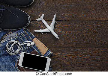 Table top view of object for traveler with technology concept background. Variety essential items on modern brown wooden office desk. Mix cloth for teenage or adult for travel with copy space.