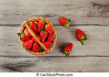 Table top view on small basket full of strawberries on wooden desk.
