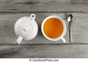Table top view on white ceramic teapot, cup of hot black tea, and silver spoon placed on gray wood desk.
