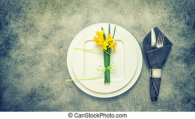 Table top with cutlery, napkin, spring flowers