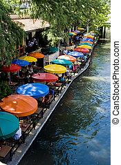 table umbrellas - multi-colored table umbrellas along the...