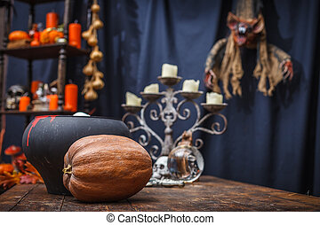 Table with a pot, pumpkin, crystal ball chandelier and to celebr