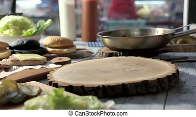 Table with burger ingredients. Sliced buns and patties. How...