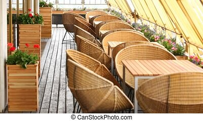 Table with chairs and flowers stand on restaurant terrace on...