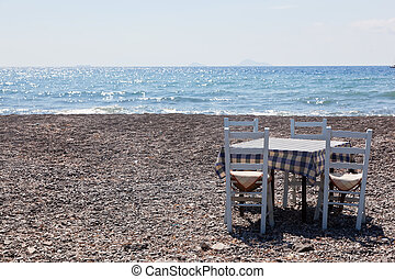 Table with chairs on the beach. Tavern in Greece, Santorini