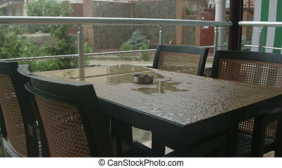 Table with chairs on the terrace in the rain