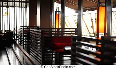 Table with chairs stands separated by baffles in restaurant lounge