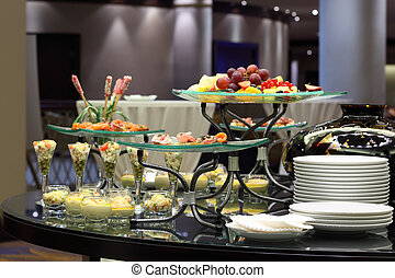 Table with cold snacks and fruits on stand and tableware on...