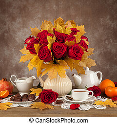 table with cups of tea, chocolates and a bouquet roses