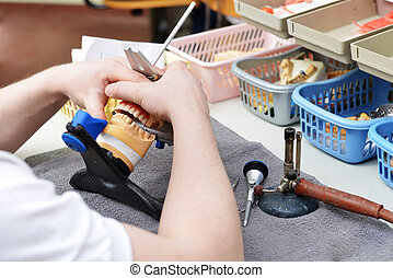 table with dental tools - dental technician working on false...