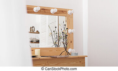 Table with makeup products and mirror near white wall. Dressing room interior