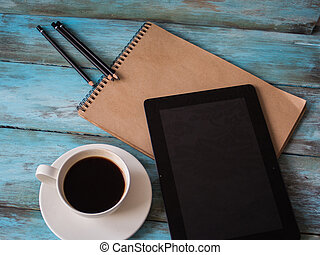 Table with modern tablet, notepad and cup of coffee